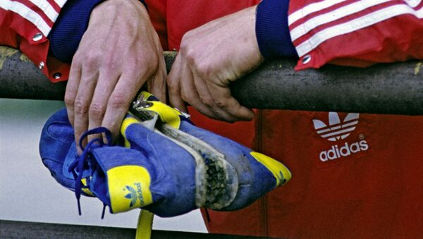 Советский спортсмен держит в руке  кроссовки Adidas - Sputnik Армения