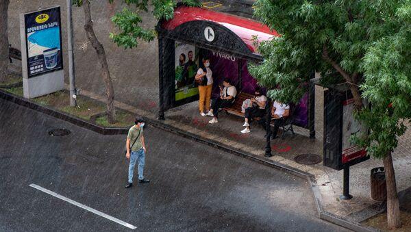 Пассажиры на автобусной остановке во время дождя - Sputnik Արմենիա