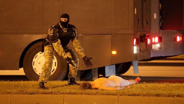 Сотрудник правоохранительных органов рядом с лежащим на земле протестующим во время столкновений после закрытия избирательных участков президентских выборов (9 августа 2020). Минск - Sputnik Армения