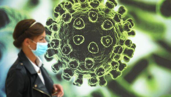 Женшина в защитной маске проходит перед баннером с изображением коронавируса - Sputnik Армения