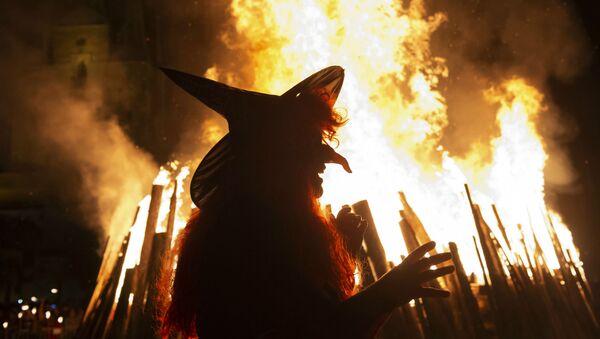 Женщина в костюме ведьмы идет перед гигантским огнем во время Вальпургиевой ночи в Эрфурте (30 апреля 2018). Германия - Sputnik Արմենիա