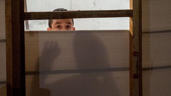 Мальчик за дверью в убежище в Степанакерте - Sputnik Армения