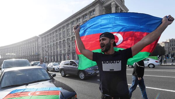 Член азербайджанской диаспоры размахивает флагом Азербайджана во время митинга на площади Независимости (11 октября 2020). Киев - Sputnik Армения