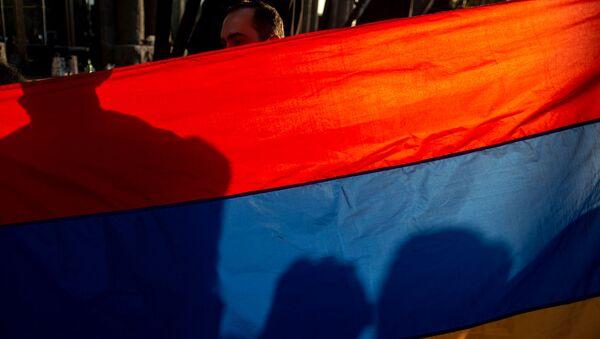 Национальный флаг Армении в руках участника акции в поддержку признания независимости Карабаха (13 октября 2020). Еревaн - Sputnik Արմենիա