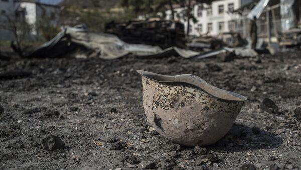 Пробитая каска на территории у госпиталя в Мартакерте, разрушенного в результате обстрела. - Sputnik Արմենիա