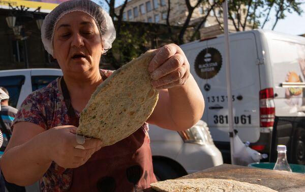 """Женщины, прибывшие из Степанакерта, готовят и продают """"женгялов хац"""" в центре Еревана (19октября 2020). Еревaн - Sputnik Армения"""