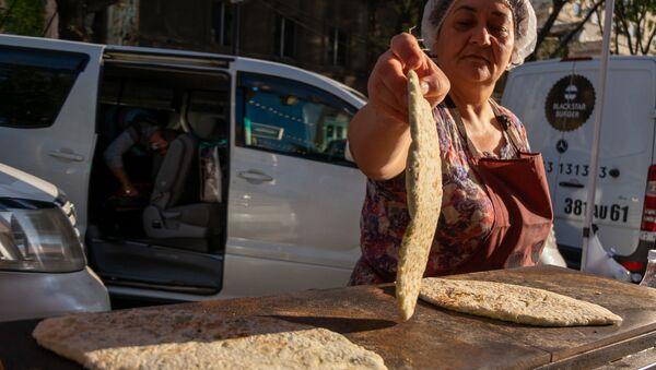 """Женщины, прибывшие из Степанакерта, готовят и продают """"женгялов хац"""" в центре Еревана (19октября 2020). Еревaн - Sputnik Արմենիա"""