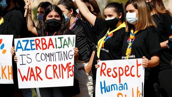 Армяно-ливанские студенты держат плакаты, призывая ООН выступить против нападений Азербайджана в Карабахe (23 октября 2020). Бейрут - Sputnik Армения