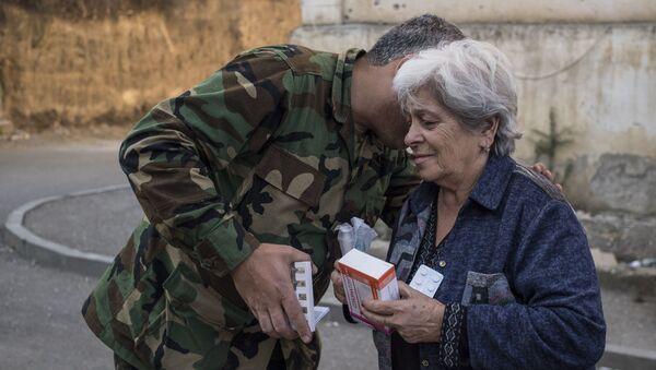 Волонтер в форме передает лекарства пожилой женщине в Степанакерте (16 октября 2020). Карабах - Sputnik Армения