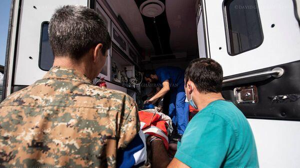 Медработники и волонтеры перевозят раненного в следствии обстрела Шуши гражданина (28 октября 2020). Карабах - Sputnik Армения