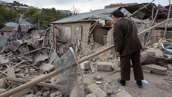 Женщина осматривает разрушенный дом на месте обстрела в Степанакерте (28 октября 2020). Карабах - Sputnik Армения
