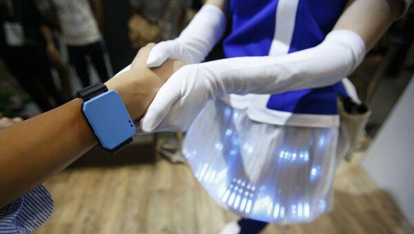Посетитель с синим браслетом пожимает руку демонстратору Panasonic во время ежегодной выставки передовых технологий CEATEC Japan (6 октября 2016). Япония - Sputnik Армения
