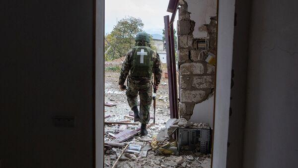 Военнослужащий возле дома, поврежденного в результате обстрела Степанакерта (6 ноября 2020). Карабах - Sputnik Армения