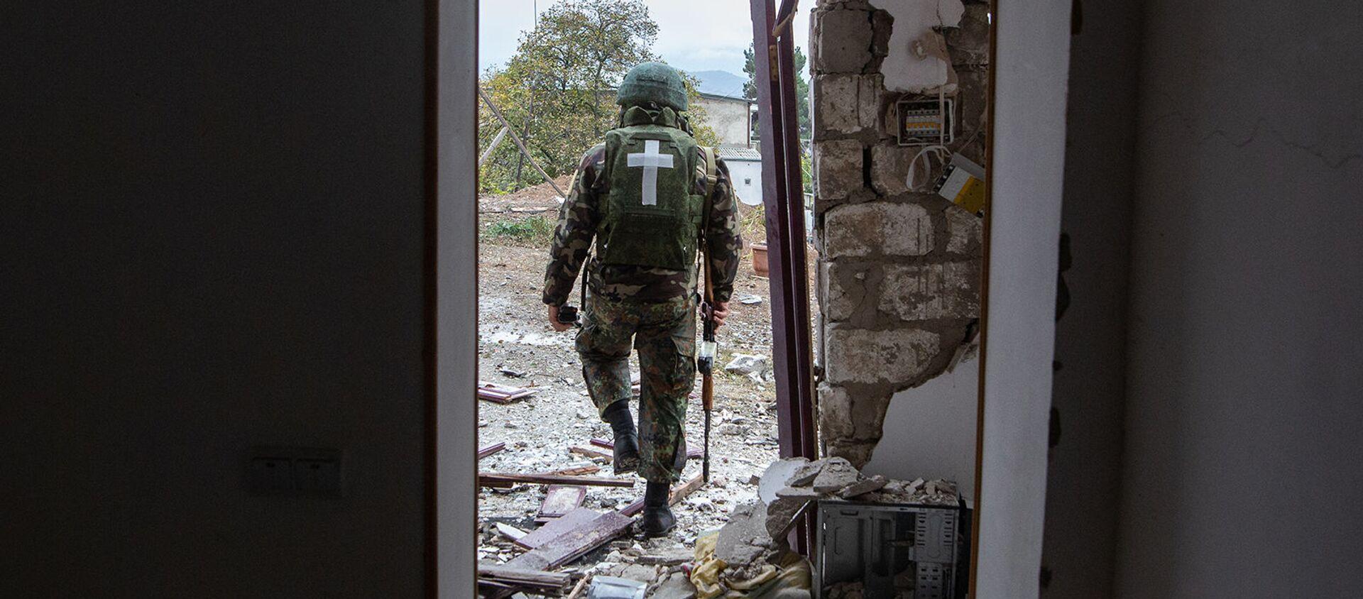 Военнослужащий возле дома, поврежденного в результате обстрела Степанакерта (6 ноября 2020). Карабах - Sputnik Армения, 1920, 13.07.2021