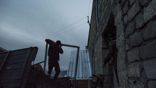Мужчины загружают личные вещи в кузов грузового автомобиля в поселке Карегах Кашатанского района (25 ноября 2020). Карабах - Sputnik Արմենիա