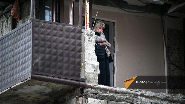 Женщина в своей квартире дома в Степанакерте, пострадавшего во время обстрела - Sputnik Արմենիա
