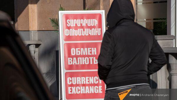 Люди проходят мимо вывески пункта обмена валюты в Ереване - Sputnik Армения