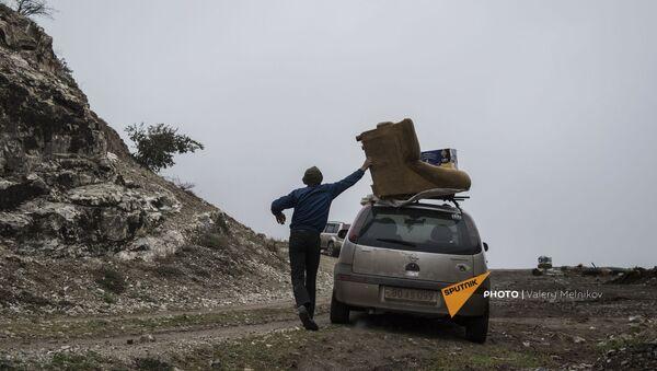 Мужчина с перегруженным вещами автомобилем покидает свой дом в городе Бердзор (30 ноября 2020). Карабах - Sputnik Արմենիա