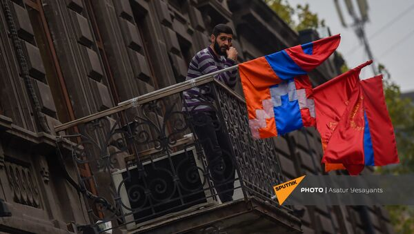 Молодой человек беседует по телефону на балконе в здании Верховного органа АРФД (3 декабря 2020). Еревaн - Sputnik Армения