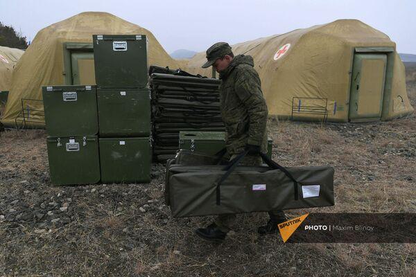Российский военнослужащий выгружает оборудование на территории мобильного полевого госпиталя неподалеку от Степанакерта (29 ноября 2020). Карабах - Sputnik Армения