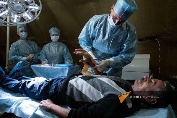 Медик оказывает помощь пациенту на базе полевого госпиталя развернутого Минобороны России на территории аэропорта в Степанакерте (1 декабря 2020). Карабах - Sputnik Армения