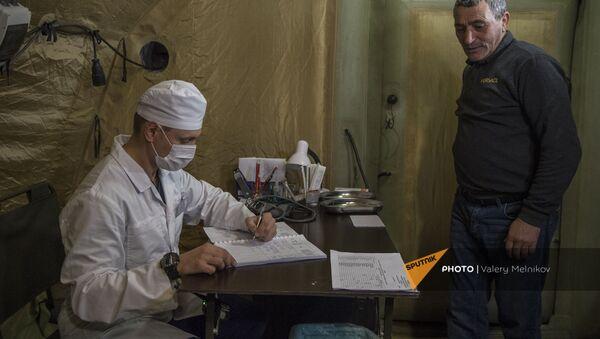 Врач проводит прием пациента на базе госпиталя развернутого Министерством обороны России на территории аэропорта в Степанакерте (3 декабря 2020). Карабах - Sputnik Армения