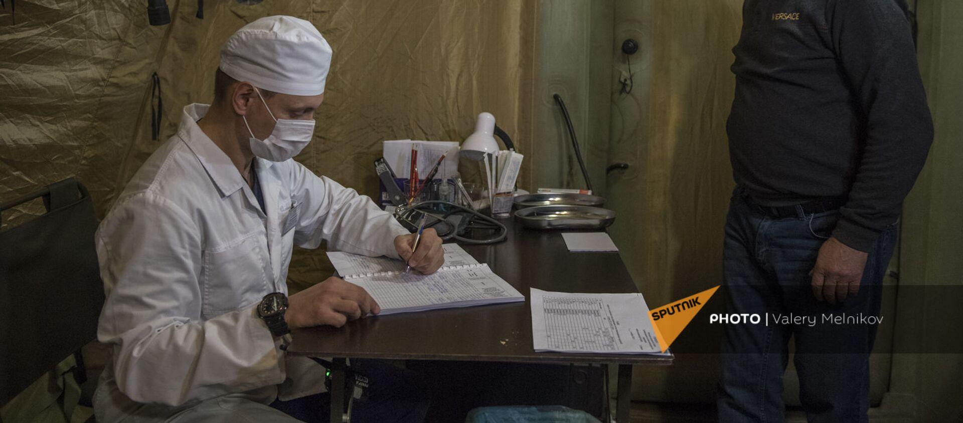Врач проводит прием пациента на базе госпиталя развернутого Министерством обороны России на территории аэропорта в Степанакерте (3 декабря 2020). Карабах - Sputnik Армения, 1920, 13.01.2021