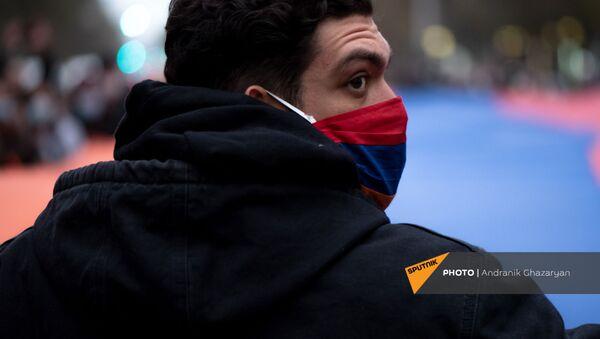 Молодой человек в маске с армянским триколором во время митинга оппозиции с требованием отставки премьер-министра (5 декабря 2020). Еревaн - Sputnik Արմենիա