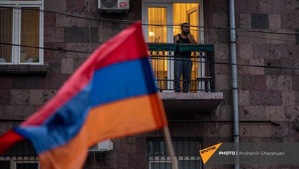 Житель столицы наблюдает за шествием оппозиции с требованием отставки премьер-министра (5 декабря 2020). Еревaн - Sputnik Армения