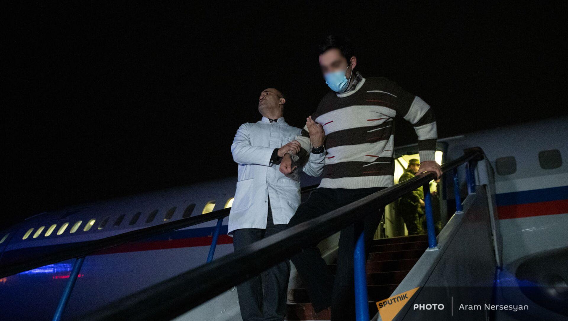 Пленные спускаются по трапу самолета в аэропорту Эребуни (14 декабря 2020). Еревaн - Sputnik Армения, 1920, 28.06.2021
