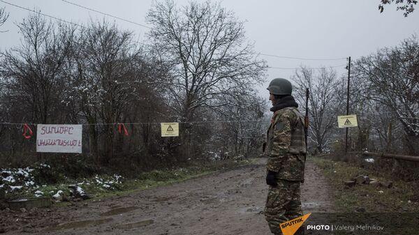 Военнослужащий армии обороны Карабаха на одной из улиц в селе Тагавард Мартунинского района (11 декабря 2020). Карабах - Sputnik Արմենիա