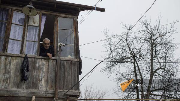 Пожилой мужчина смотрит из окна своего дома в селе Тагавард Мартунинского района (11 декабря 2020). Карабах - Sputnik Армения
