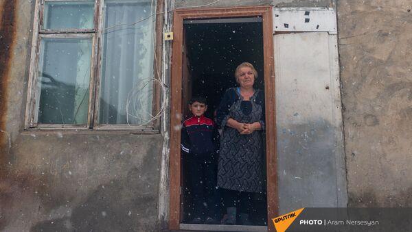 Жительница села Сотк Гаяне Ераносян на пороге дома с маленьким Гором (18 декабря 2020). Варденис - Sputnik Արմենիա