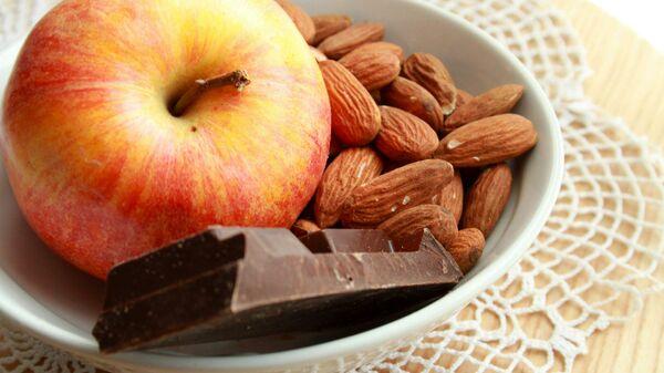 Яблоко с темным шоколадом и миндалем в тарелке - Sputnik Արմենիա