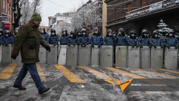 Мужчина проходит мимо полицейского кордона на перекрестке проспекта Тиграна Меца и улицы Мелика Адамяна (24 декабря 2020). Еревaн - Sputnik Արմենիա