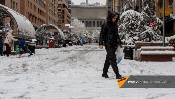 Женщина проходит по неочищенному Северному проспекту (24 декабря 2020). Еревaн - Sputnik Армения