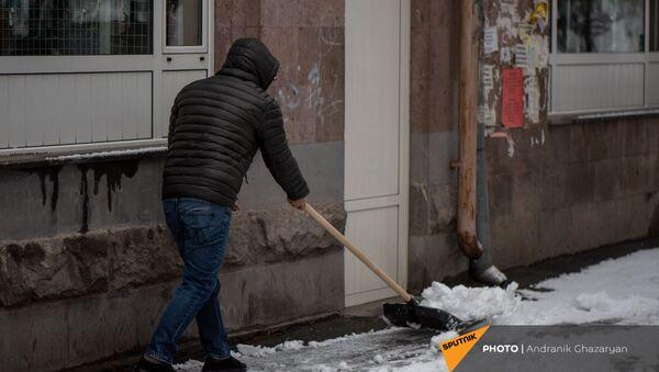 Молодой человек очищает от снега улицу - Sputnik Արմենիա