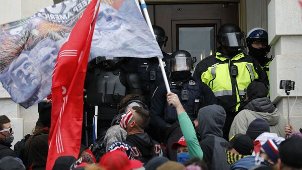 Участники акции протеста сторонников действующего президента США Дональда Трампа штурмуют двери Конгресса (7 декабря 2021). Вашингтон - Sputnik Армения