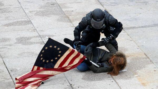 Офицер полиции задерживает участника акции протеста сторонников действующего президента США Дональда Трампа у здания Конгресса (7 декабря 2021). Вашингтон - Sputnik Армения
