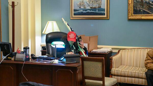 Сторонник президента США Дональда Трампа сидит в кабинете спикера Палаты представителей Нэнси Пелоси во время акции протеста в Капитолии (6 декабря 2021). Вашингтон - Sputnik Армения