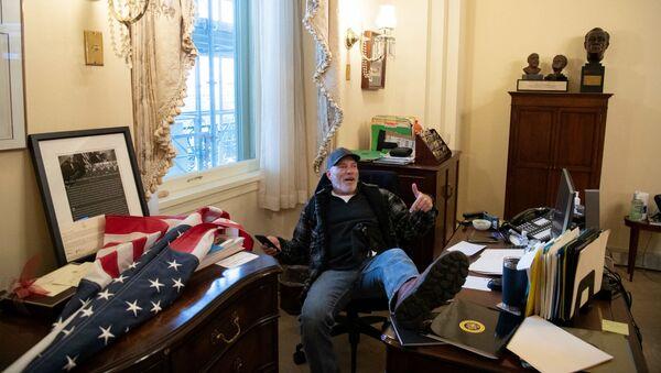 Cторонник президента США Дональда Трампа, Ричард Барнетт, сидит в кабинете спикера палаты представителей США Нэнси Пелоси во время акции протеста в Капитолии (6 декабря 2021). Вашингтон - Sputnik Армения