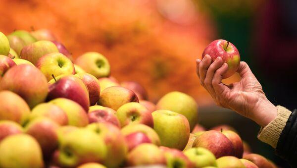 Яблоки в руке покупателя в магазине - Sputnik Արմենիա