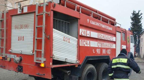 Сотрудник МЧС Армении рядом с пожарной машиной - Sputnik Արմենիա