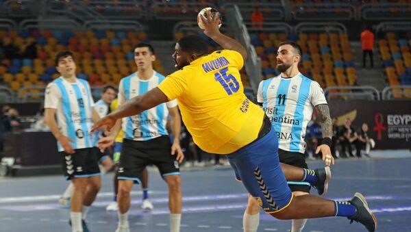 Гандболист Готье Мвумби делает бросок во время матча чемпионата мира по гандболу 2021 года между сборными командами группы D Аргентины и ДР Конго (15 января 2021). Каир - Sputnik Армения