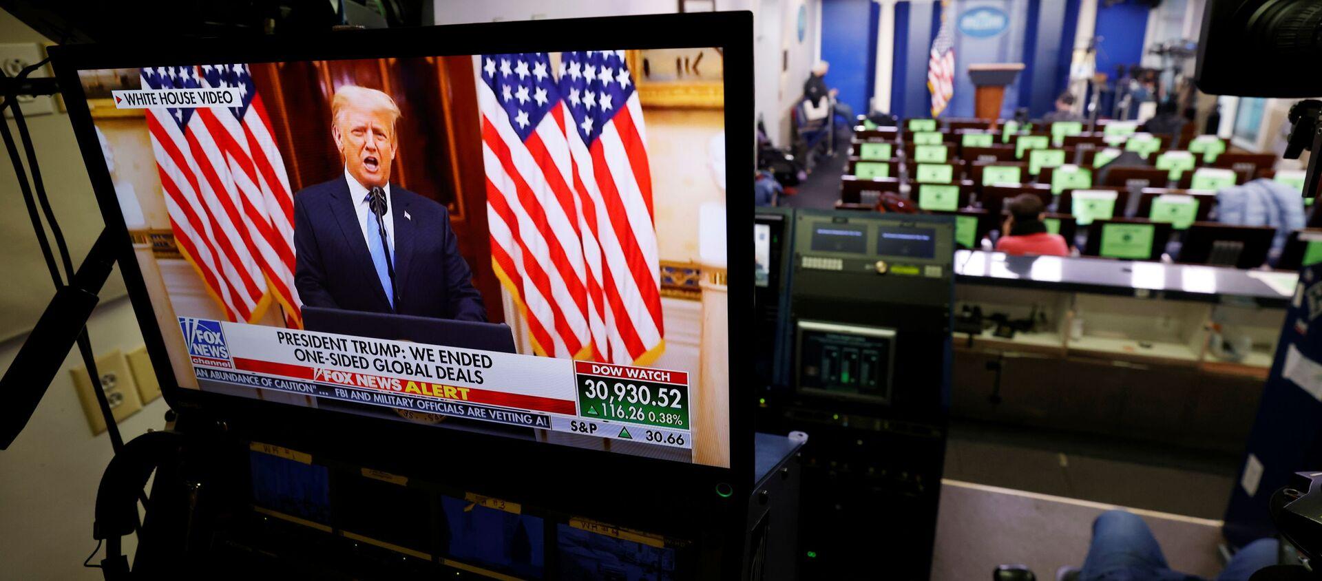 Президент США Дональд Трамп на телеэкране в последний день своего пребывания в должности в Вашингтоне - Sputnik Армения, 1920, 21.01.2021