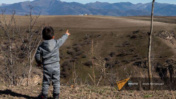 Сын Армена Бадаляна показывает на азербайджанский пост из села Неркин Хндзореск, Сюник - Sputnik Արմենիա