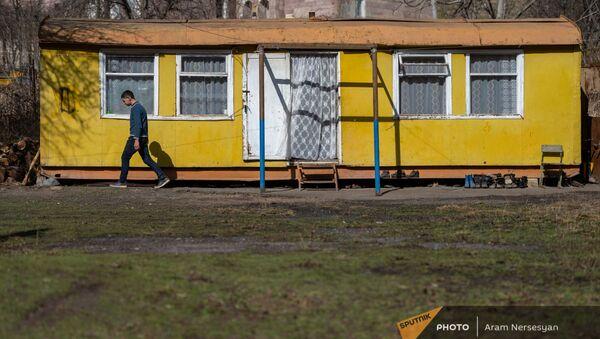 Молодой житель села Неркин Ханд в Сюникской области на фоне своего домика - Sputnik Армения