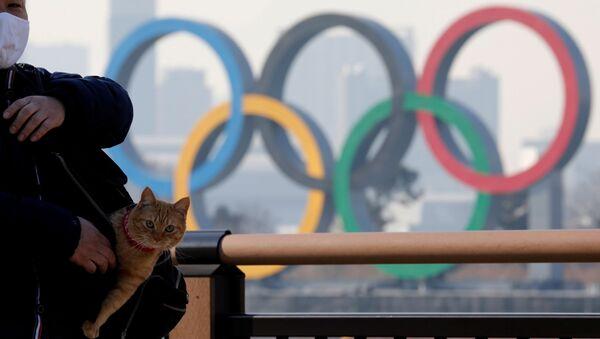 Мужчина с котом в сумке на фоне олимпийских колец в Токио - Sputnik Армения