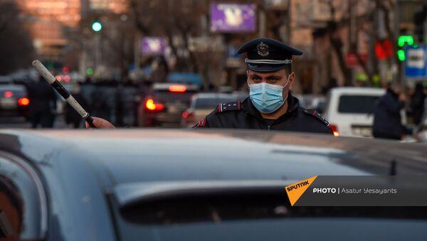 Полицейский регулировщик указывает помогает автомобилистам во время шествия протеста оппозиции по центральным улицам столицы (23 февраля 2021). Еревaн - Sputnik Армения