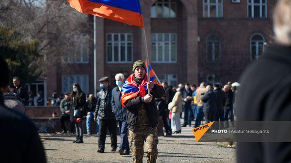 Оппозиционер с флагами на плечах и в руках перед началом акции оппозиции на перекрытом проспекте Баграмяна (26 февраля 2021). Еревaн - Sputnik Армения